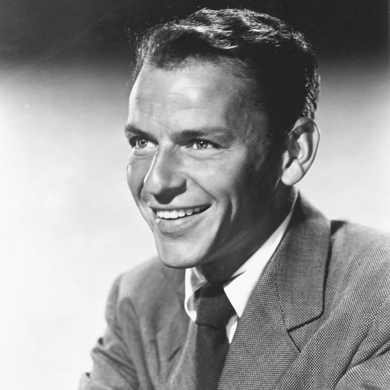Frank Sinatra wearing a suit and tie smiling at the camera: Before crooning