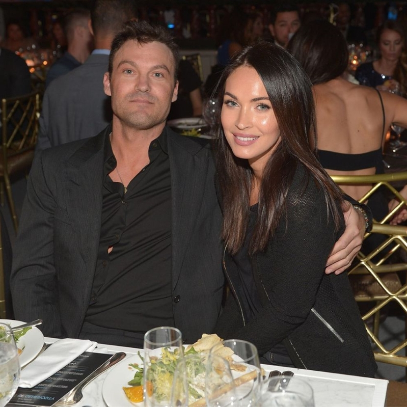 Megan Fox, Brian Austin Green sitting at a table posing for the camera: Megan Fox and Brian Austin Green | Charley Gallay/WireImage