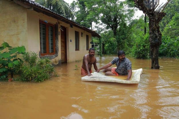 Slide 11 of 12: Men pass through flood waters at Eloor area in Ernakulam district, in the south Indian state of Kerala, on August 9, 2019. - Floods that have killed more than 20 people forced the closure of Kochi international airport on August 9 as the south Indian state of Kerala confronted a second straight year of crisis level downpours. (Photo by STR / AFP)        (Photo credit should read STR/AFP/Getty Images)