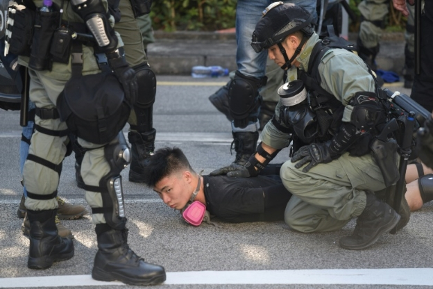 a group of people in uniform sitting next to a child: Police detain a demonstrator during protests in Hong Kong's Tuen Mun district