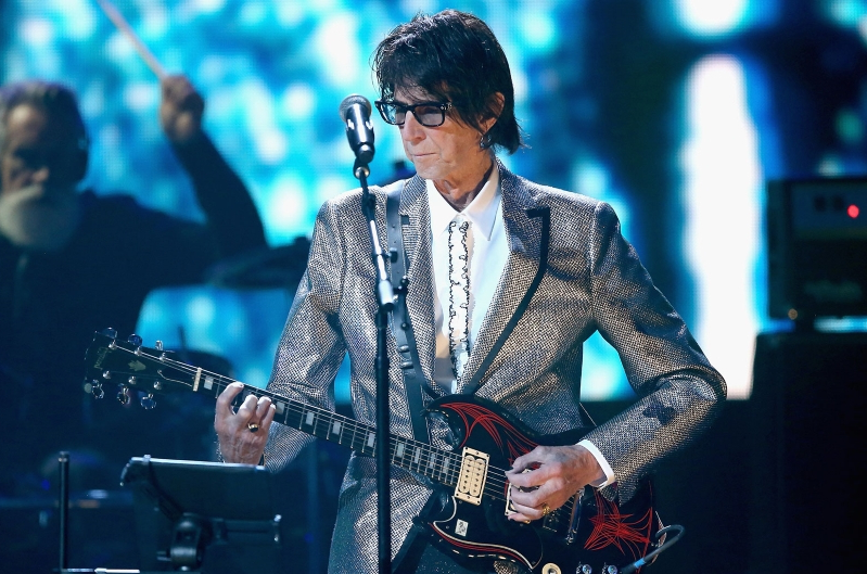 a person standing on a stage: Ric Ocasek of The Cars