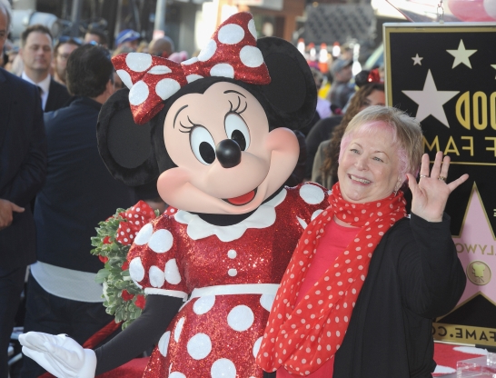 Slide 22 of 163: HOLLYWOOD, CA - JANUARY 22:  Voice actress Russi Taylor, who has voiced Minnie Mouse since 1986, poses with Minnie Mouse during a star ceremony in celebration of the 90th anniversary of Disney's Minnie Mouse at the Hollywood Walk of Fame on January 22, 2018 in Hollywood, California.  (Photo by Albert L. Ortega/Getty Images)