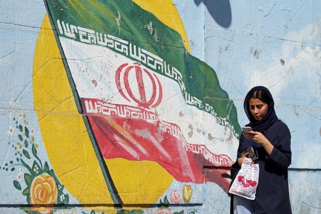 Slide 25 of 115: Iranians women walk past a mural of depicting the Iranian national flag in a street in capital Tehran, September 19, 2019. - Foreign Minister Mohammad Javad Zarif accused Iran's foes of agitating for war, as Washington and its Gulf allies stepped up their rhetoric over twin attacks on Saudi oil facilities. (Photo by STR / AFP)        (Photo credit should read STR/AFP/Getty Images)