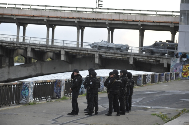 Slide 39 of 115: Ukrainian Police and Armoured personnel carrier (APC) guard at Kiev's metro system bridge on September 18, 2019, following an incident with an armed man. - A gunman fired shots from his car after blocking a major road bridge in the Ukrainian capital Kiev and threatened to blow it up, police said. Kiev police said the man had stopped traffic on the bridge over the Dnipro river and was