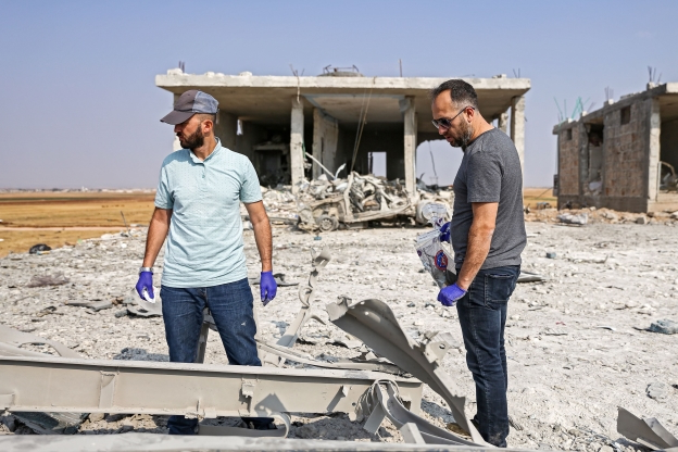 Slide 73 of 115: Turkish forensic experts collect samples as they inspect the scene of a rigged-car explosion in the Syrian town of al-Rai, held by pro-Turkish Syrian fighters, in the north of Aleppo province along the border with Turkey, on September 16, 2019. (Photo by Nazeer Al-khatib / AFP) (Photo credit should read NAZEER AL-KHATIB/AFP/Getty Images)