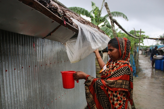 Slide 74 of 115: SHYAMNAGAR, SATKHIRA, KHULNA, BANGLADESH - 2019/09/16: A woman collects rainwater by using a plastic sheet under tin roof, rainwater is the main source of drinking water at the Shyamnagar villages. Bangladesh is one of the countries most vulnerable to the effects of climate change. The regular and severe natural hazards that Bangladesh already suffers from tropical cyclones, river erosion, flood, landslides and drought are all set to increase in intensity and frequency as a result of climate change. (Photo by Sultan Mahmud Mukut/SOPA Images/LightRocket via Getty Images)