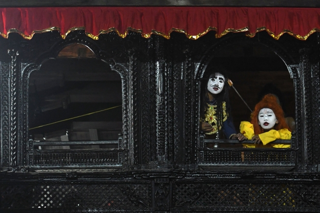 Slide 87 of 115: Nepali young artists with painted face look out from a window before performing in a play based on Hindu mythology at Basantapur Durbar Square on the second to last day of the 'Indra Jatra' Hindu festival in Kathmandu on September 16, 2019. (Photo by PRAKASH MATHEMA / AFP) (Photo credit should read PRAKASH MATHEMA/AFP/Getty Images)