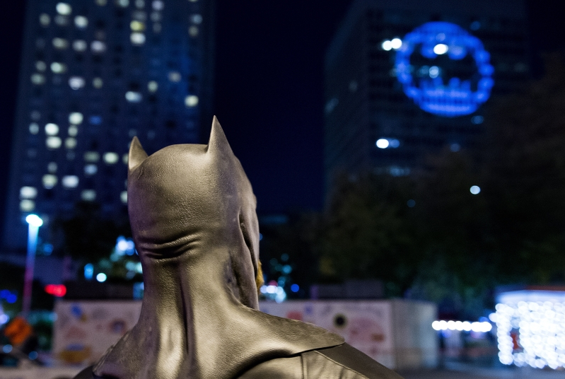 A man dressed as Batman looks up towards the Batman signal projected onto a building to celebrate Batman Day in Montreal, Saturday, Sept. 21, 2019. The night sky all over the world is lighting up Saturday with an illumination of the famed bat insignia to mark a special anniversary for Batman. DC Comics is carrying off a celebration of Batman Day to mark the 80th anniversary of the appearance of crimefighter Bruce Wayne and his masked hidden identity. (Graham Hughes/The Canadian Press via AP)