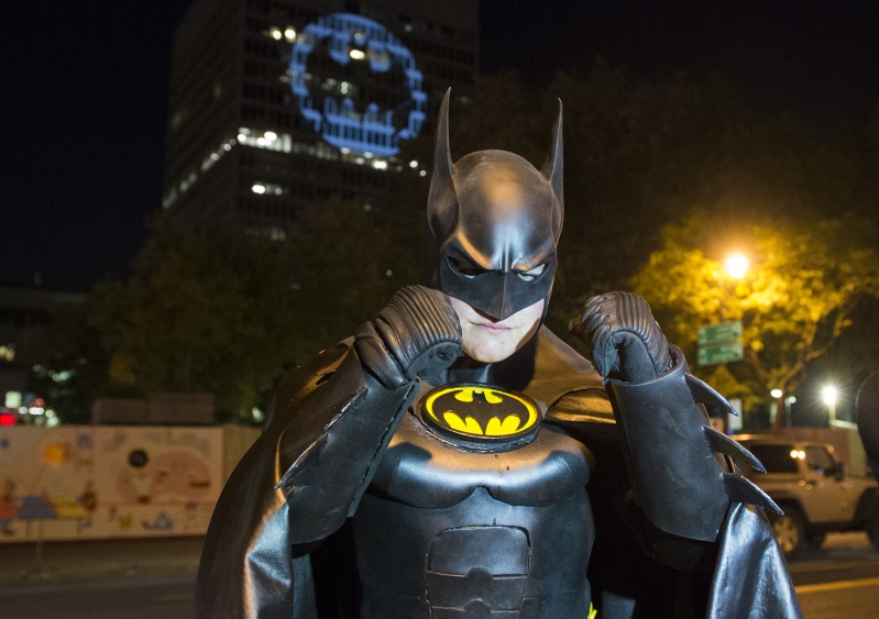 A man dressed in a Batman costume poses for a photo in front of the Batman signal projected onto a building to celebrate Batman Day in Montreal, Saturday, Sept. 21, 2019. The night sky all over the world is lighting up Saturday with an illumination of the famed bat insignia to mark a special anniversary for Batman. DC Comics is carrying off a celebration of Batman Day to mark the 80th anniversary of the appearance of crimefighter Bruce Wayne and his masked hidden identity. (Graham Hughes/The Canadian Press via AP)
