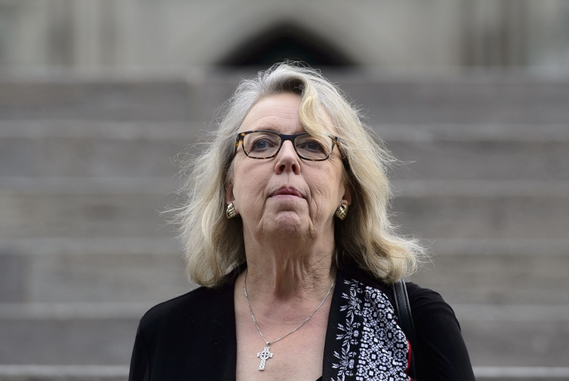 Elizabeth May wearing sunglasses: Green Party Leader Elizabeth May makes her way from Parliament Hill in Ottawa on Tuesday, June 18, 2019.