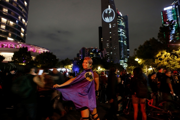 Stephanie Salgado poses with her cape during the lighting of the Bat signal commemorating Batman's 80th anniversary in Mexico City, Saturday, Sept. 21, 2019. (AP Photo/Ginnette Riquelme)