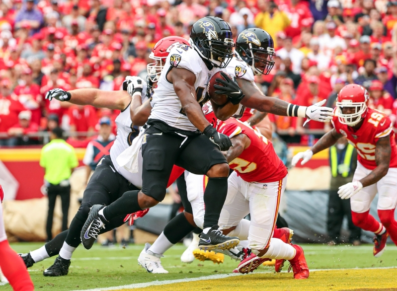 a group of people playing football on a field: Baltimore Ravens running back Mark Ingram (21) carries to ball to score a touchdown against the Kansas City Chiefs during the first quarter at Arrowhead Stadium on September 22, 2019.