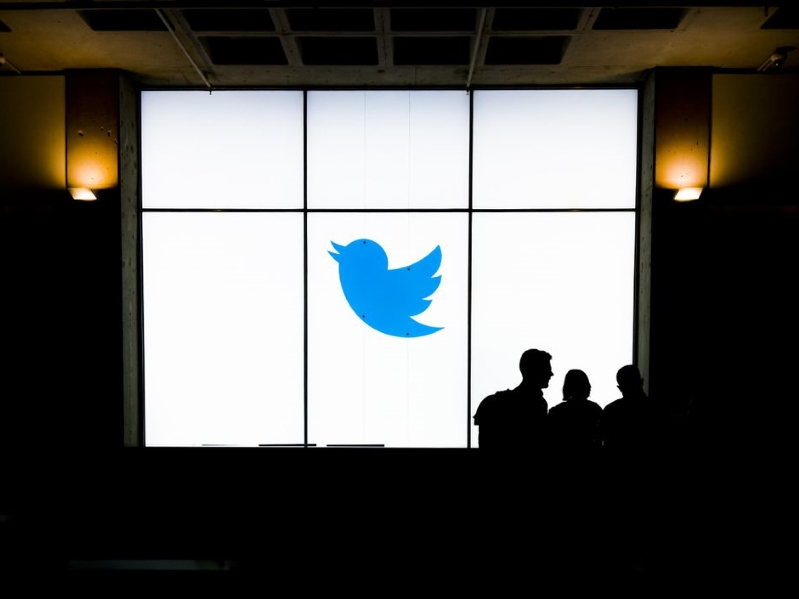 a group of people standing in front of a window: Twitter has a new policy about financial scams. James Martin/CNET