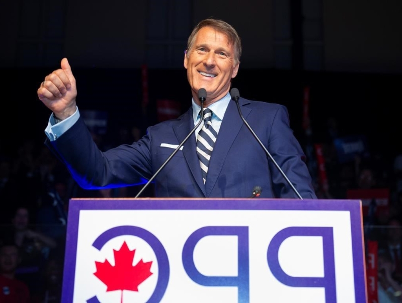 Maxime Bernier holding a sign: Maxime Bernier, leader of the People's Party of Canada, raises his thumb at the launch of his campaign Sunday, Aug. 25, 2019 in Sainte-Marie, Que.