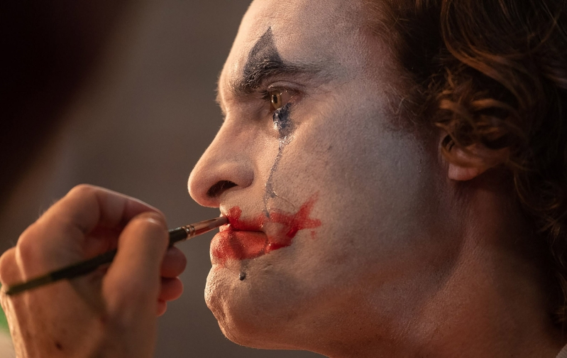 a man brushing his teeth: Joaquin Phoenix as Arthur Fleck in Todd Phillips'