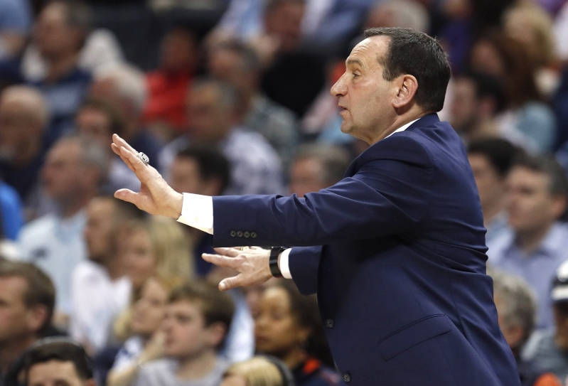 a man standing in front of a crowd: Duke head coach Mike Krzyzewski instructs his players during the first half against Syracuse in the quarterfinals of the ACC Tournament at the Specturm Center in Charlotte, N.C., on March 14, 2019.