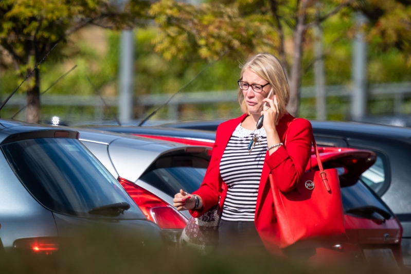 a woman in a red car: Devastated staff left Thomas Cook's head office on Monday. Photo: SWNS