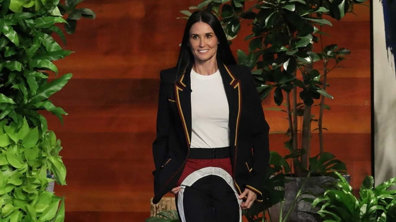 Demi Moore standing in front of a plant
