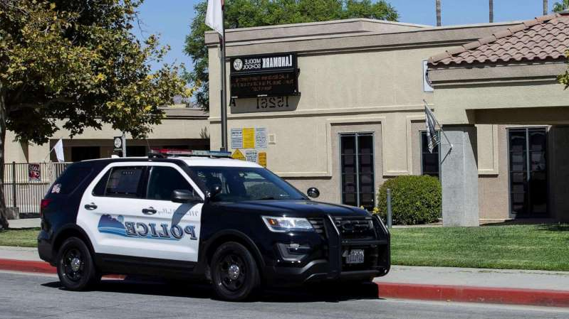 a car parked in front of a building: A police car sits in front of the Landmark Middle School in Moreno Valley, Calif., Sept. 18, 2019.