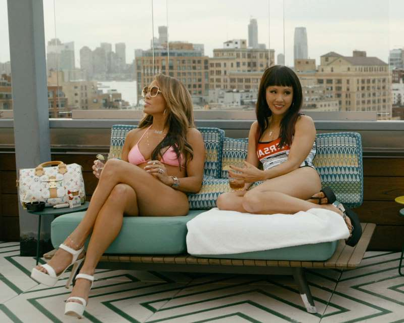 a woman sitting on a bench: Constance Wu (left) and Jennifer Lopez are single moms, strip-club co-workers and partners in crime in the crowd-pleasing