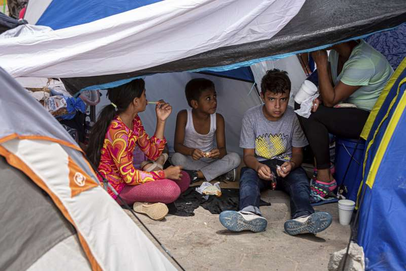 a group of people sitting in a tent: On August 24, 2019, immigration lawyers working with the Atlanta-based group Lawyers for Good Government, attempted to inform hundreds of asylum seekers of their legal rights after they had been sent back to Matamoros, as part of the Trump's