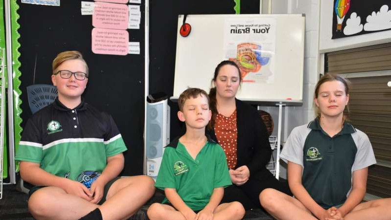 a group of people sitting posing for the camera: St Joseph's Catholic College uses an emotional wellbeing app after high-energy activities. (Supplied: Ginny Edwards)