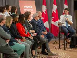 a group of people sitting in front of a crowd: Liberal Leader Justin Trudeau speaks with trauma care workers during a discussion on gun violence gun control on Sept. 30, 2019 in Toronto.
