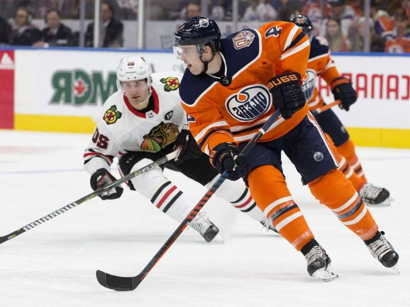 a hockey game in the snow: The Edmonton Oilers' Kris Russell (4) battles the Chicago Blackhawks' Brandon Saad (20) during second period NHL action at Rogers Place in Edmonton on Thursday, Nov. 1, 2018.
