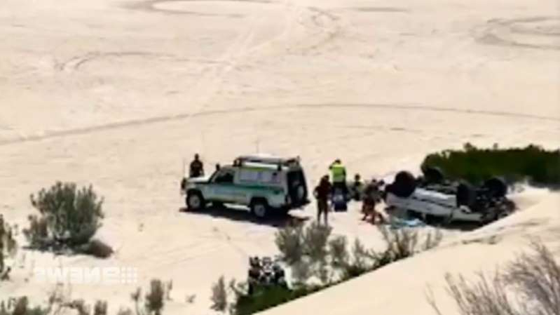 a man riding a snowboard down a snow covered slope: The Nissan Patrol's roof was crushed when it rolled down a steep sand dune.