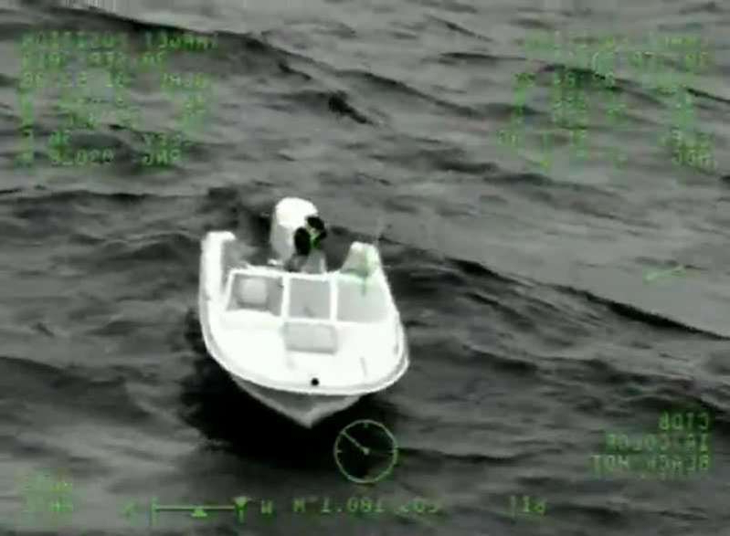 a small boat in a body of water: Man, boys rescued from boat