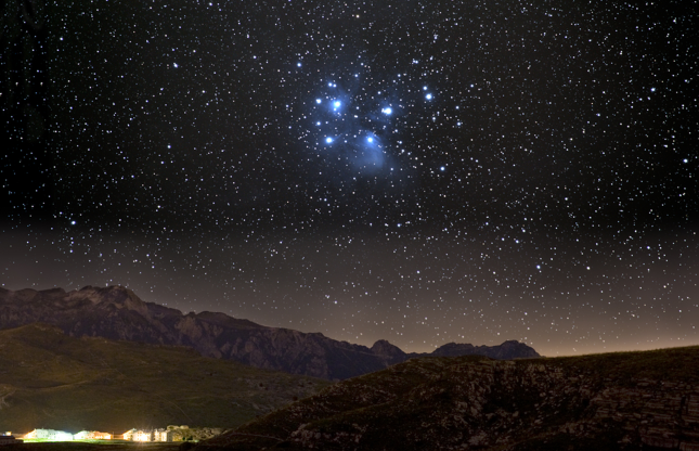 Slide 10 of 13: The Pleiades star cluster over a mountain village.