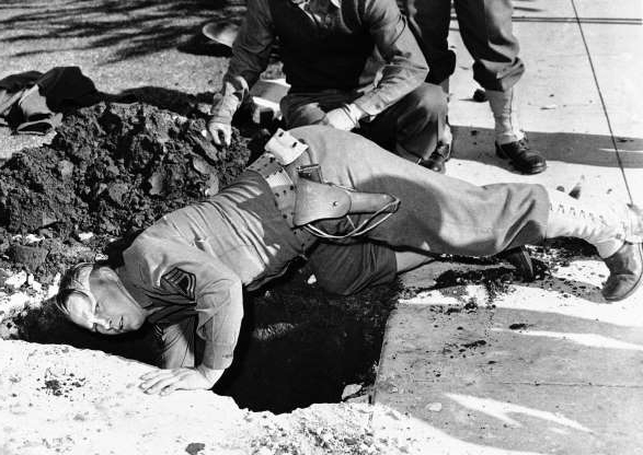 Slide 2 of 13: An army demolition squad moved right in to take things over after an unexploded anti-aircraft shell fell in the yard of George Watson at Santa Monica, Calif., Feb. 26, 1942, when it was thrown up in the great barrage of fire from army guns during an air raid alarm in the Los Angeles area on February 25. Sergeant C.M. Weathers reaches down to remove it. (AP Photo)