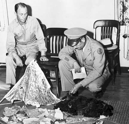 Slide 3 of 13: Brig. General Roger M. Ramey, Commanding General of 8th Airforce, and Col. Thomas J. Dubose, 8th Airforce Chief of Staff, identify metallic fragments found by a farmer near Roswell, New Mexico, as pieces of a weather balloon. This is the basis of the Roswell Incident, the supposed crash of an alien spacecraft.