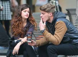 a man and a woman sitting on a bench: Cigarettes could be banned in Melbourne as one councillor pushes for the entire CBD to go smoke-free (file image)