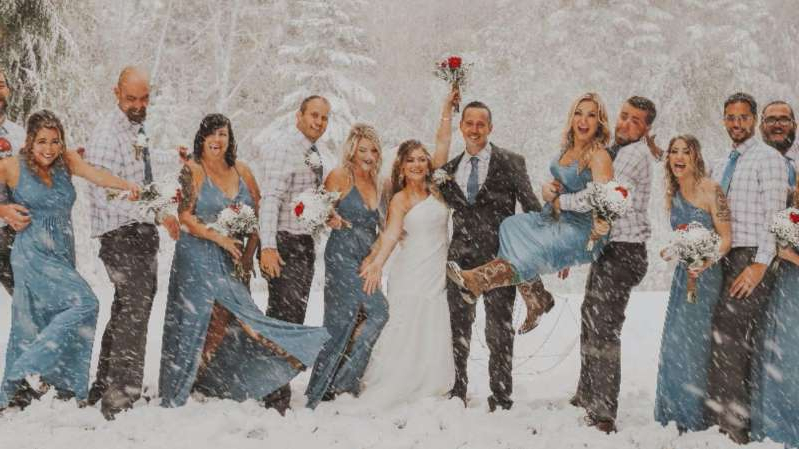 a group of people posing for the camera: Sean and Brittany Tuohy managed to smile and share a kiss as the flakes fell.