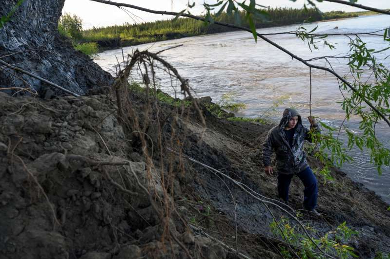 a man standing next to a river: Andrey Danilov, a part-time hunter of ancient mammoth tusks, treks through an area of the Zyryanka River in Russia's Siberia that has been made rich in ivory by thawing permafrost.