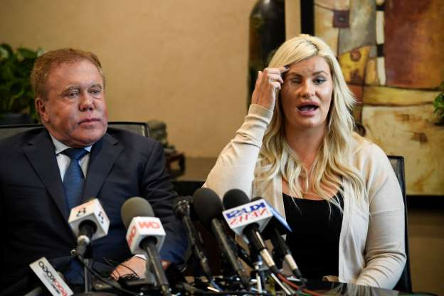 Chelsea Romo, left, pulls the her hair out of the way to show her left eye at a news conference as her attorney James Frantz looks on Thursday, Oct. 3, 2019, in San Diego. Romo lost her left eye in the Las Vegas shooting. Two years after a shooter rained gunfire on country music fans from a high-rise Las Vegas hotel, MGM Resorts International reached a settlement that could pay up to $800 million to families of the 58 people who died and hundreds of others who were injured, attorneys announced Thursday. (AP Photo/Denis Poroy)