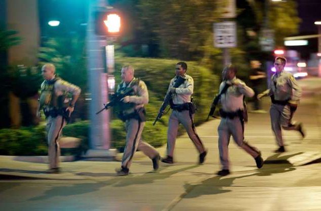 FILE - In this Oct. 1, 2017, file photo, police run toward the scene of a shooting near the Mandalay Bay resort and casino on the Las Vegas Strip in Las Vegas. Two years after a shooter rained gunfire on country music fans from a high-rise Las Vegas hotel, MGM Resorts International reached a settlement that could pay up to $800 million to families of the 58 people who died and hundreds of others who were injured, attorneys announced Thursday, Oct. 3, 2019. (AP Photo/John Locher, File)