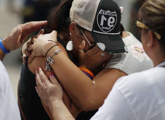 FILE - In this Oct. 1, 2018 file photo people embrace Norma Felix at a prayer service on the anniversary of the Oct.1, 2017 mass shooting in Las Vegas. Two years after a shooter rained gunfire on country music fans from a high-rise Las Vegas hotel, MGM Resorts International reached a settlement that could pay up to $800 million to families of the 58 people who died and hundreds of others who were injured, attorneys announced Thursday, Oct. 3, 2019. (AP Photo/John Locher,File)