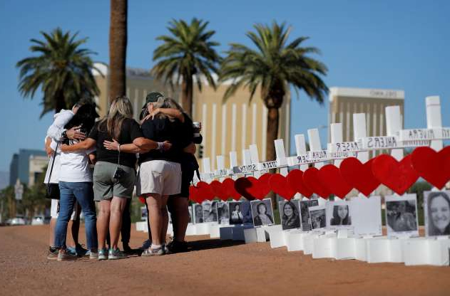 FILE - In this Oct. 1, 2019, file photo, people pray at a makeshift memorial for shooting victims in Las Vegas, on the anniversary of the mass shooting two years earlier. Two years after a shooter rained gunfire on country music fans from a high-rise Las Vegas hotel, MGM Resorts International reached a settlement that could pay up to $800 million to families of the 58 people who died and hundreds of others who were injured, attorneys announced Thursday, Oct. 3, 2019. (AP Photo/John Locher, File)
