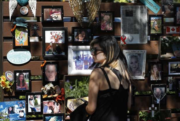 People visit a memorial garden for victims of a mass shooting in Las Vegas, Thursday, Oct. 3, 2019, in Las Vegas. Two years after a shooter rained gunfire on country music fans from a high-rise Las Vegas hotel, MGM Resorts International reached a settlement that could pay up to $800 million to families of the 58 people who died and hundreds of others who were injured, attorneys said Thursday. (AP Photo/John Locher)