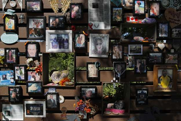 Photographs adorn a wall at a memorial garden for victims of a mass shooting in Las Vegas, Thursday, Oct. 3, 2019, in Las Vegas. Two years after a shooter rained gunfire on country music fans from a high-rise Las Vegas hotel, MGM Resorts International reached a settlement that could pay up to $800 million to families of the 58 people who died and hundreds of others who were injured, attorneys said Thursday. (AP Photo/John Locher)