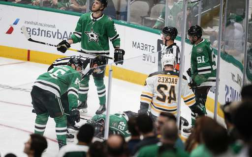 a group of hockey players posing for a picture: Dallas Stars defenseman Roman Polak (45) lies on the ice after going head-first into the boards during the second period of the team's NHL hockey game against the Boston Bruins, Thursday, Oct. 3, 2019, in Dallas. Polak was taken off the ice on a stretcher. (AP Photo/Brandon Wade)