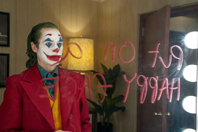 a man wearing a suit and tie: Movie review: Controversy aside, 'Joker' is all setup, no punchline.