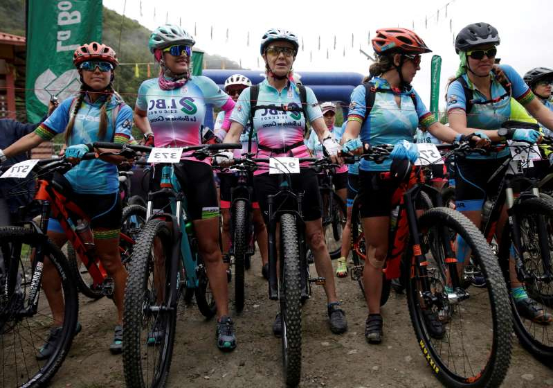 a group of people riding on the back of a bicycle: Mirtha Munoz a 70-year-old runner participates in the Sky Race, Bolivia's toughest cycling competition
