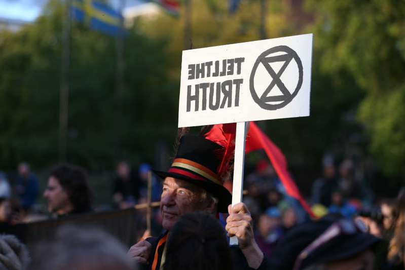 a man holding a sign: Extinction Rebellion protesters holding an opening ceremony at Marble Arch (Jonathan Brady/PA)