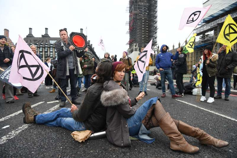a group of people sitting and standing in front of a crowd: A pair of protesters chained together at the neck on Westminster Bridge, during an Extinction Rebellion (XR) protest in Westminster, London (Victoria Jones/PA)