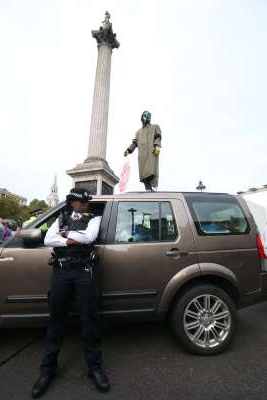 a man standing in front of a car: Protesters on top of vehicles blocking the road in Trafalgar Square (Jonathan Brady/PA
