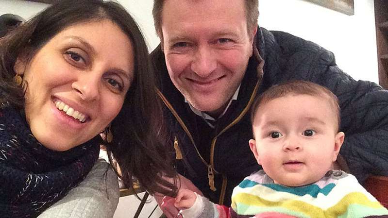 a person holding a baby posing for the camera: Jailed British mother Nazanin Zaghari-Ratcliffe, seen here before her imprisonment, with her husband Richard Ratcliffe and their daughter Gabriella (Family handout/PA)
