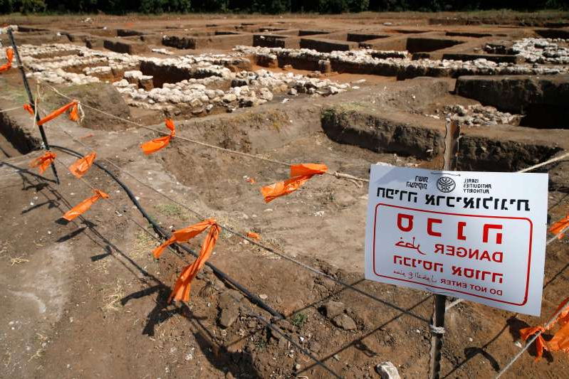 an orange sign on a dirt road: A picture taken on October 06, 2019, shows a warning sign and safety cordons at the archaeological site of En Esur (Ein Asawir) where a 5000-year-old city was uncovered, near the Israeli town of Harish.